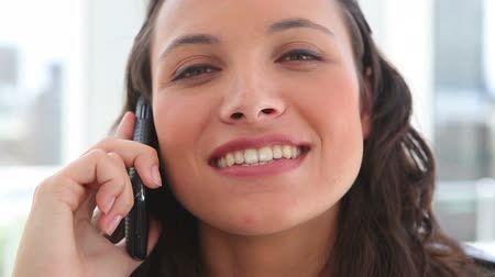 брюнет : Businesswoman laughing during a phone call in an office
