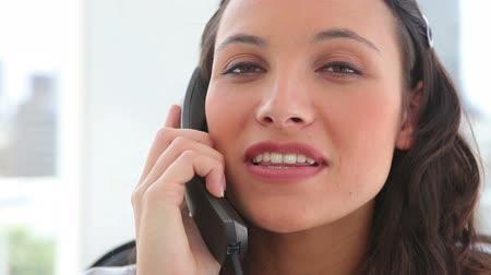 брюнет : Happy businesswoman making a call in an office