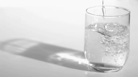 claro : Trickle of water in a super slow motion empty a glass against a grey background