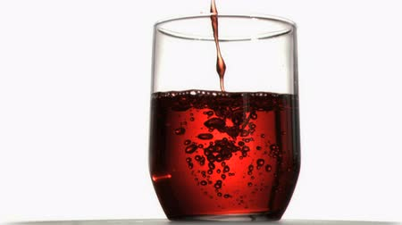 enchimento : Red liquid in super slow motion flowing in a glass against a white background Vídeos