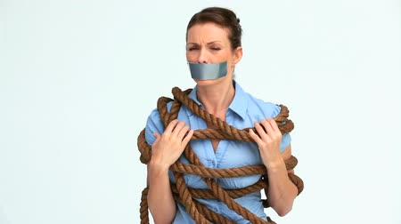 лента : Woman with tape on the mouth and attached with a rope against white background Стоковые видеозаписи