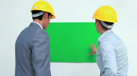poszter : Architects talking in front of a blank space on the wall while wearing safety helmet