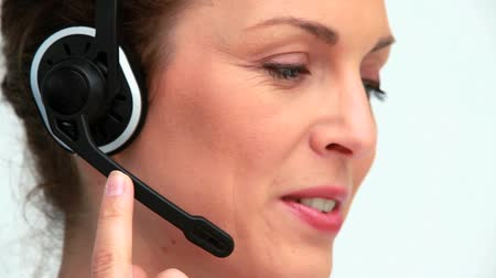 segít : Businesswoman using a headset against white background