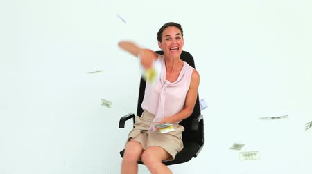 amarrado : Businesswoman throwing banknotes in the air while sitting on a chair against white background