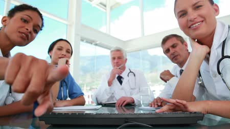 сотрудники : Medical team looking at camera as computer screen in a bright office