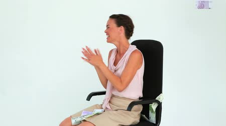 amarrado : Businesswoman sitting on a chair with banknotes falling from the sky in studio