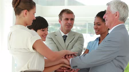 homem de negócios : Business people joining hands together in a bright office