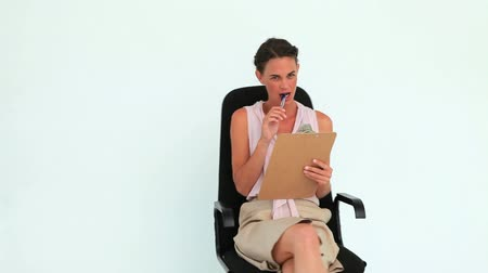 стулья : Woman holding a clipboard turning on her chair against white background Стоковые видеозаписи