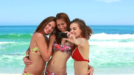 obrázky : Three women taking a group photo at the beach while they wear bikinis Dostupné videozáznamy