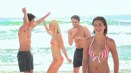 mężczyźni : Four friends partying at the beach as one girl faces the camera Wideo