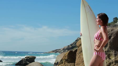 surf : Woman holding her surfboard as she looks at the water at the beach