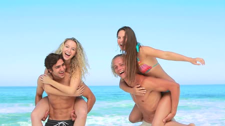 дружба : Two men giving two women piggy-backs while at the beach