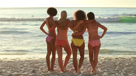 дружба : A group of girls sand together and look at the water while holding each other