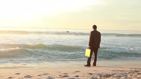 poça de água : Businessman standing on the shore letting the waves wet him