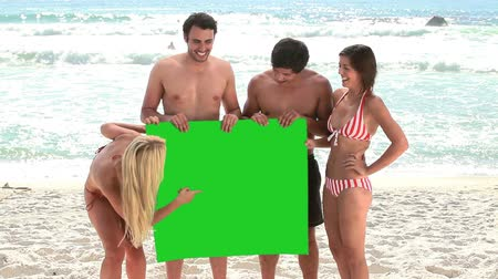 bordo : Smiling friends holding a blank poster together on the beach Stock Footage