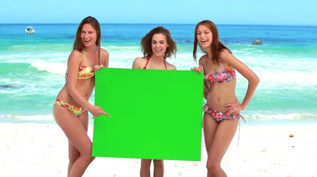 blank : Women holding a blank poster while laughing on the beach