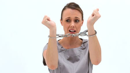 kajdanki : Brunette woman wearing handcuffs against a white background