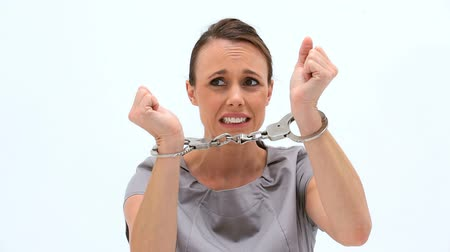 kajdanki : Serious woman wearing handcuffs against a white background