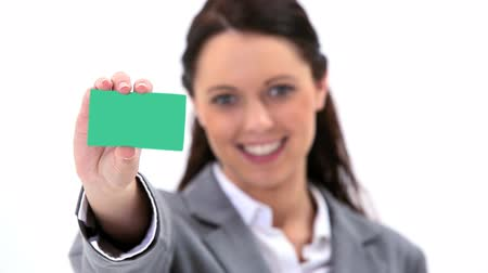 wizytówka : Smiling brunette holding a business card against a white background
