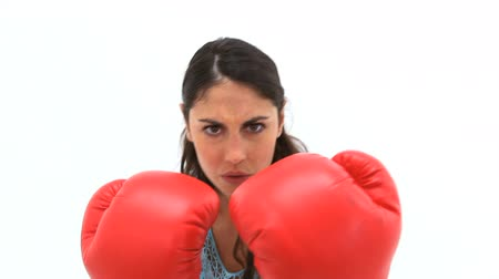 zuřivý : Serious brunette woman boxing with red gloves against a white background
