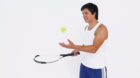 ракетка : Man does rebounds with a tennis ball on a racket against white background Стоковые видеозаписи