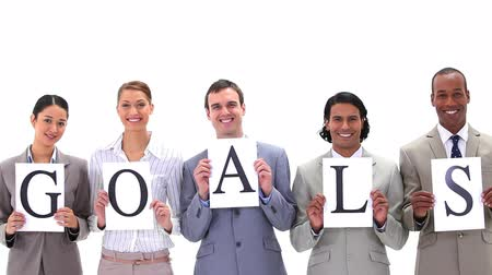 poszter : Business people holding posters with the word GOALS a against white background