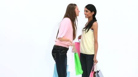 bochecha : Friends kissing while holding shopping bags against white background