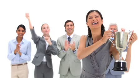 sampiyonlar : Woman holding a trophy with co-workers applauding against a white background Stok Video