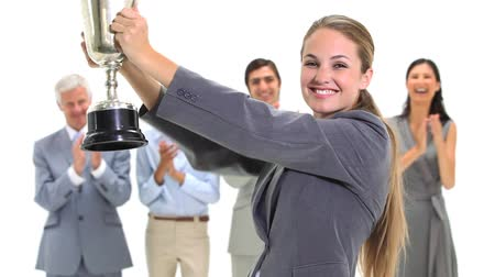 trofej : Blonde businesswoman holding a trophy against a white background