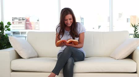nogi : Happy woman reading a book in her living room