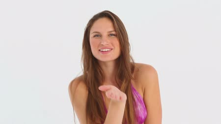 csók : Brunette haired woman in a bikini blows a kiss against white background Stock mozgókép