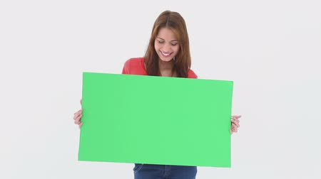 znak : Beautiful woman holding a blank poster against white background Wideo