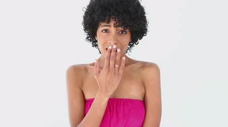 surprised : Woman with frizzy hair putting her hand on her mouth against white background