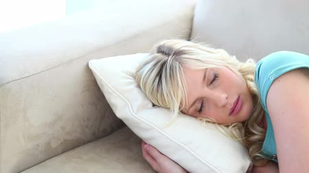 resting : Young blonde woman sleeping on a sofa