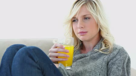içme : Sick woman drinking orange juice on a couch