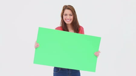 holding : Brunette haired woman dancing with a blank poster against a white background