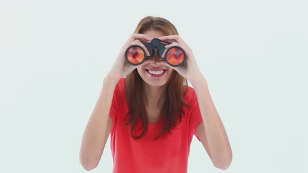 át : Brunette haired woman looking through binoculars against white background Stock mozgókép