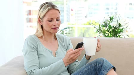 receber : Blonde drinking coffee and sending text message in a living room Stock Footage