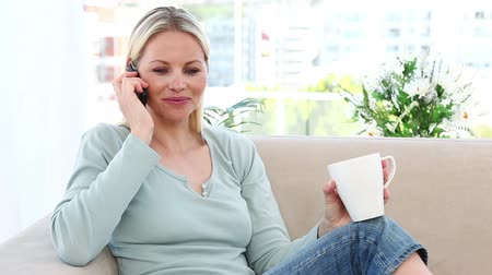 telefone celular : Woman on the phone holding a mug in a living room Stock Footage