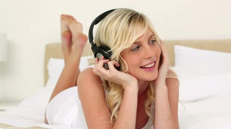 yatarken : Blonde haired woman listening to music in her bed Stok Video