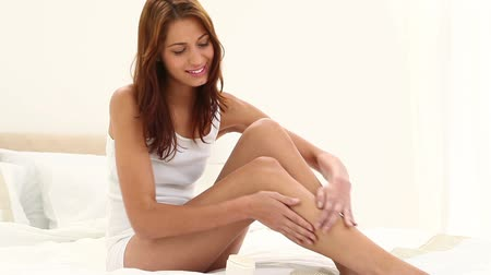 nogi : Brunette haired woman applying moisturizer on her legs while sitting on her bed