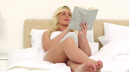 ler : Young blonde woman reading a book while lying on her bed