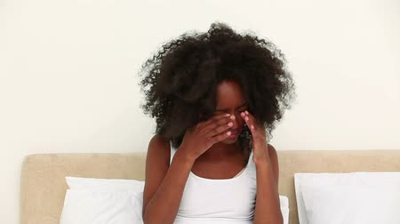 heir : Black woman rubbing her eyes when she wakes up in her bedroom Stock Footage