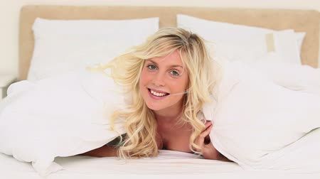 double happiness : Beautiful young blonde haired woman lifting her duvet in her bed