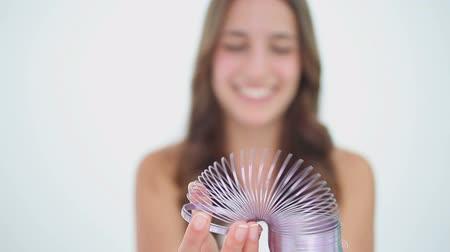 toy : Happy brunette woman playing with a metal spring against a white background