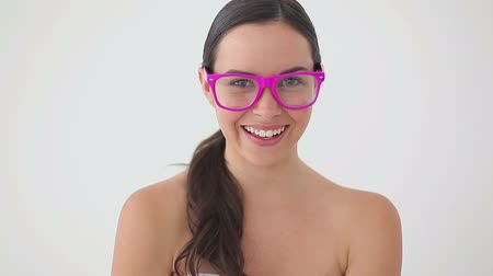 ношение : Smiling brunette woman wearing pink glasses against a white background