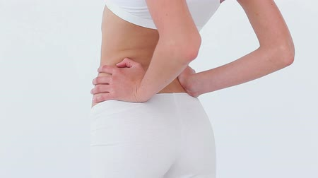 arka görünüm : Woman massaging her lower back against a white background Stok Video