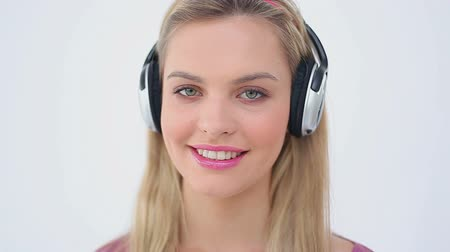giyme : Happy woman listening to music while laughing against a white background Stok Video