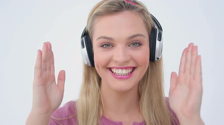 ношение : Blonde woman dancing while listening to music against a white background