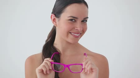 ношение : Smiling woman wearing pink glasses while laughing against a white background